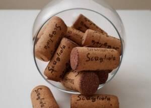 A Wine Glass Holding Scagliola & Figlio Wine Corks
