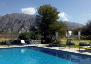 tukma large swimming pool and sunbeds against amazing mountains