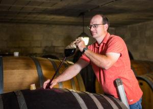 Taking out wine from oak barrels for tasting at Weingut Grenzhof-Fiedler.