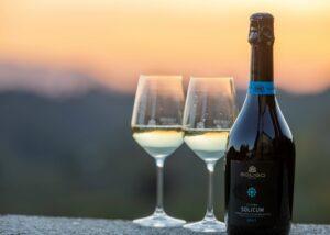 a bottle of wine with two wine glasses at Cantina Colli Del Soligo