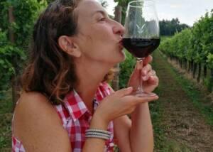 a lady having wine in the vineyard of Tenuta Valdomini S.Agricola