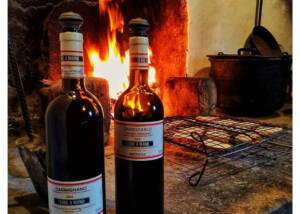 A couple of Wine Bottles of Fattoria Di Bachhereto in front of FIreplace