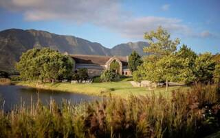 vineyard and main building of sumaridge estates beside a lake