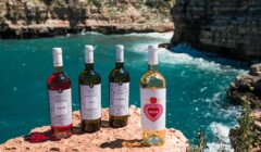 four bottles of wine by tenuta giustini near a lake
